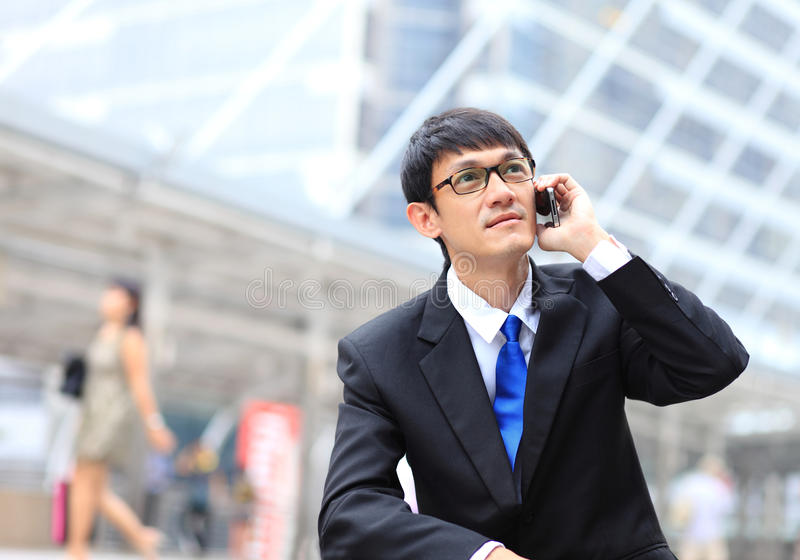 Man on smart phone - young business man. Casual urban profession. Al businessman using smartphone smiling happy outside office building. Handsome man wearing royalty free stock photography