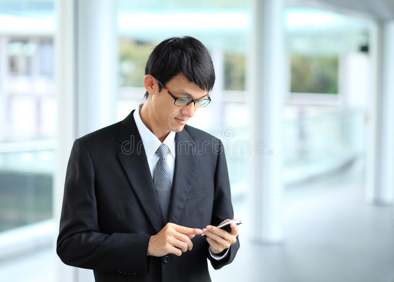 Man on smart phone - young business man. Casual urban profession. Al businessman using smartphone smiling happy outside office building. Handsome man wearing royalty free stock image