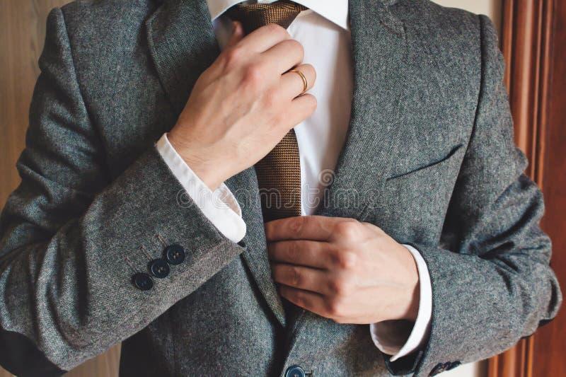 Man in smart suit wearing wedding ring adjusting tie. Elegant man in smart suit wearing gold wedding ring adjusting tie with hands stock image