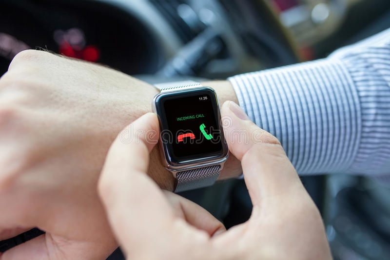 Man with smart watch and incoming call in thr car. Man with smart watch on the hand and incoming call in the screen driving a car stock image