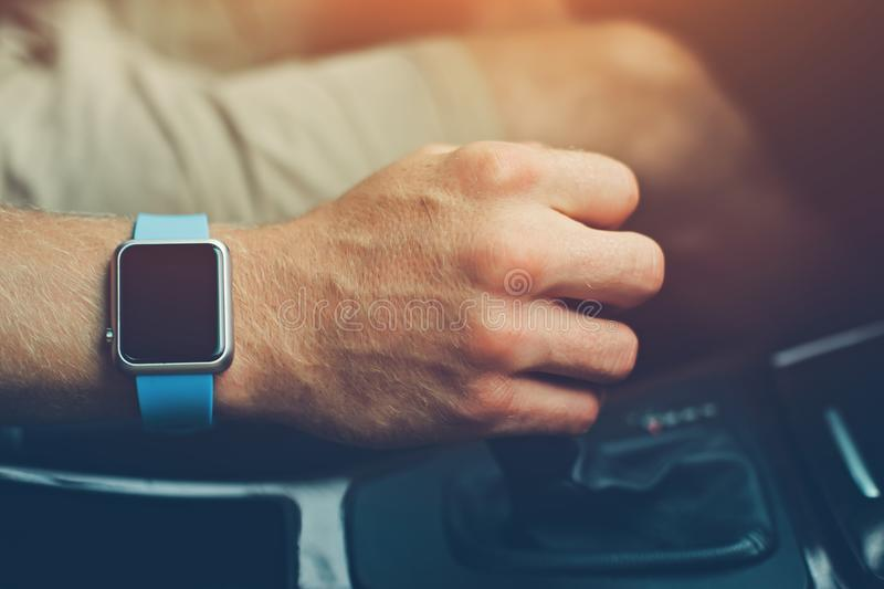 Man with smart watch on the wrist driving a car. Intentional sun glare stock photo