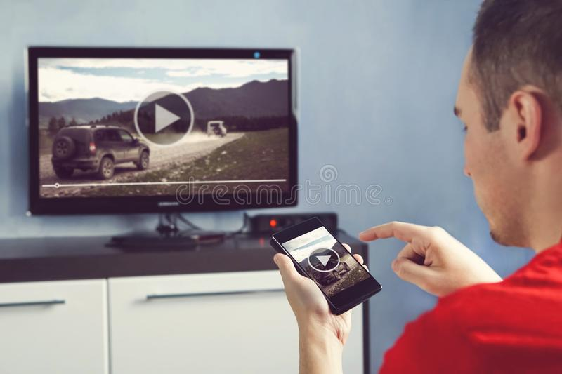 Man With Smartphone Connected To A TV Watching Video At Home. Transfer video from phone to TV screen. Modern gadgets. Information transfer between devices over royalty free stock images
