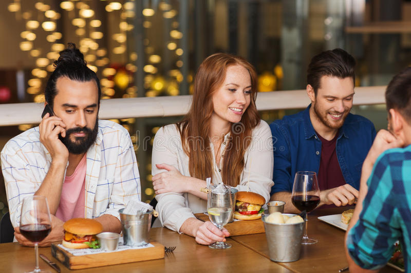 Man with smartphone and friends at restaurant stock photos