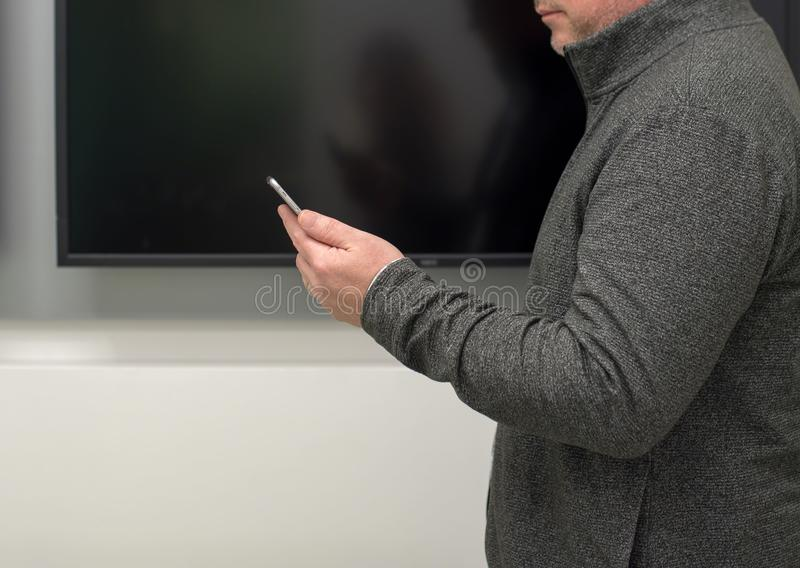 Man with smartphone in front of blank screen in meeting room stock images
