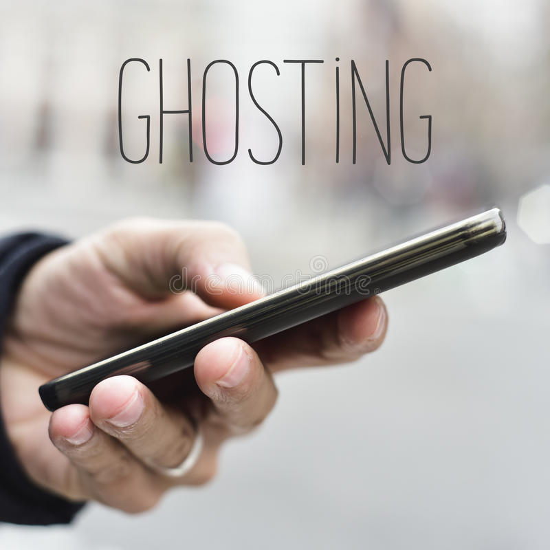 Man with smartphone and text ghosting. Closeup of a young caucasian man using a smartphone in the street and the word ghosting stock image