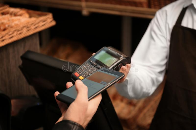 Man with smartphone using payment terminal at shop. Closeup royalty free stock photography