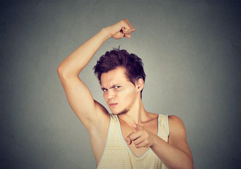 Man smelling armpit stinks bad odor pointing finger at camera stock photo
