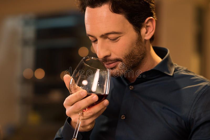 Man smelling red wine. Handsome young man smelling red wine before drinking it. Young man drinking red wine in a luxury restaurant. Handsome young man tasting a stock photography