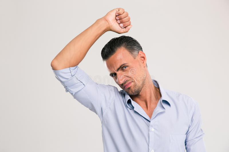 Man smelling sniffing his armpit stock photography