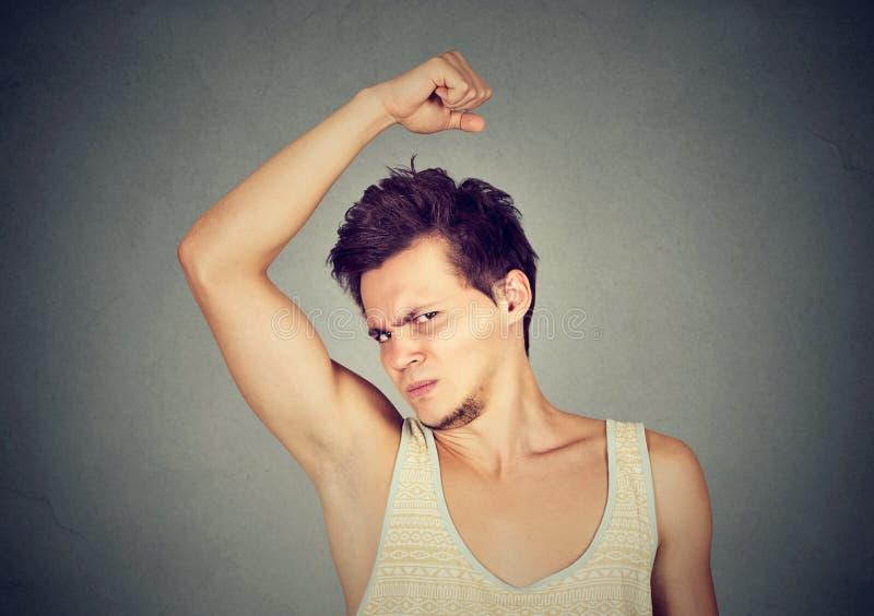 Man, smelling, sniffing his armpit, something stinks bad, foul odor royalty free stock image