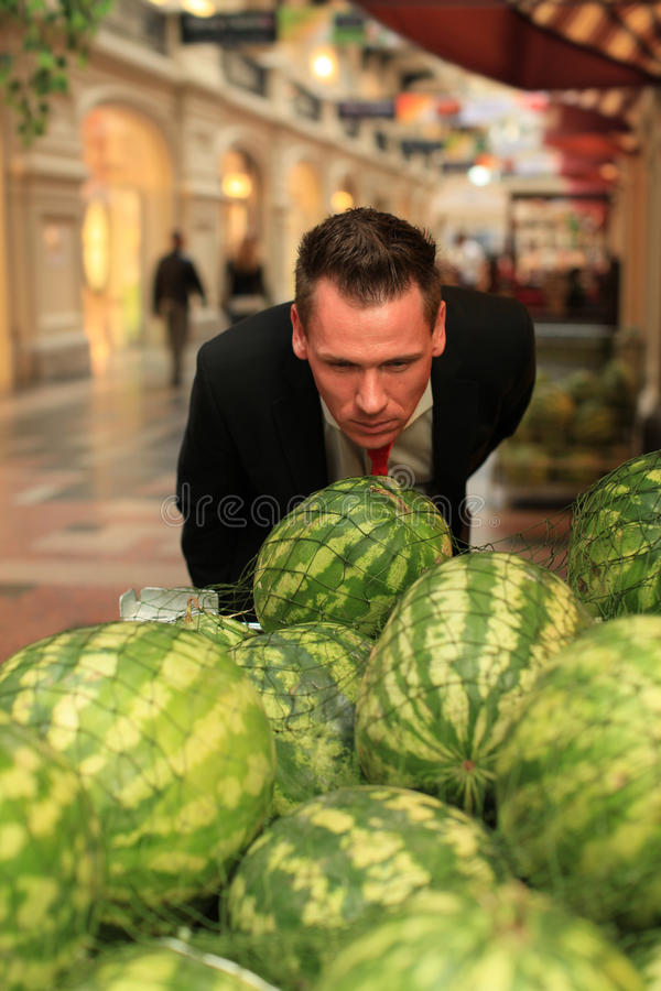 Man Smelling Watermellons In Shopping-centre Royalty Free Stock Photography