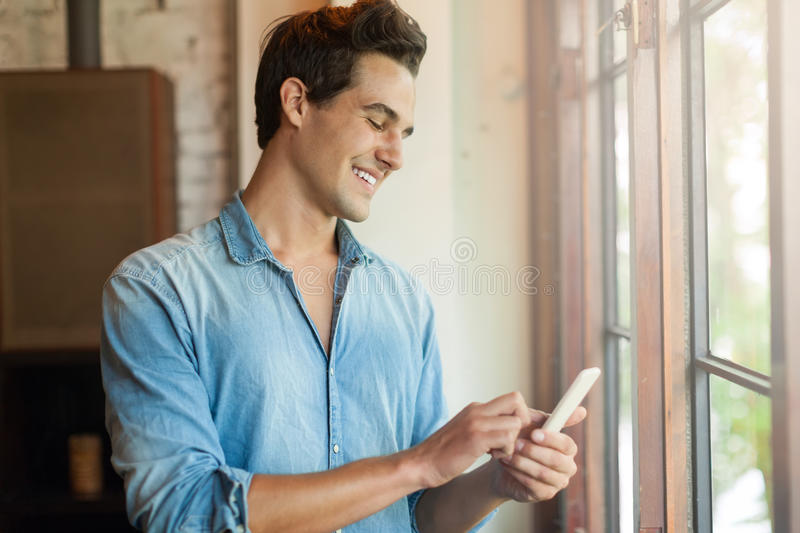 Man Smile Using Smart Phone Call, Communication. On Line Social Message Near Window royalty free stock photography