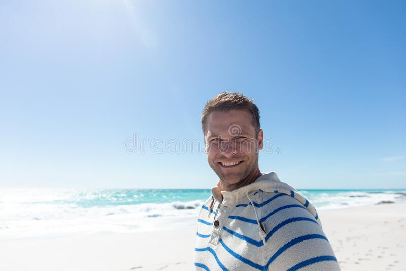Man smiling at the beach. Front view of a Caucasian man standing on the beach with blue sky and sea in the background, smiling to camera royalty free stock image