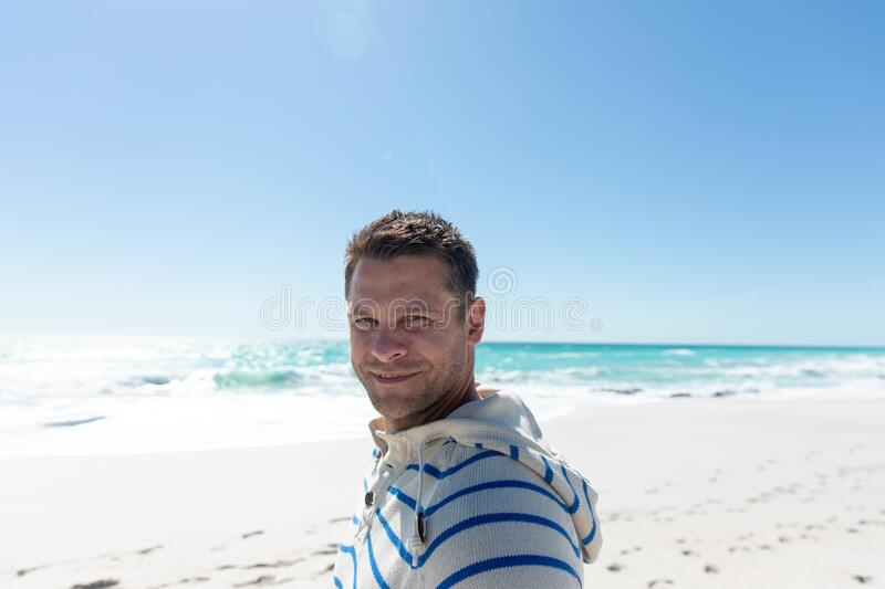 Man smiling at the beach. Front view of a Caucasian man standing on the beach with blue sky and sea in the background, smiling to camera royalty free stock images