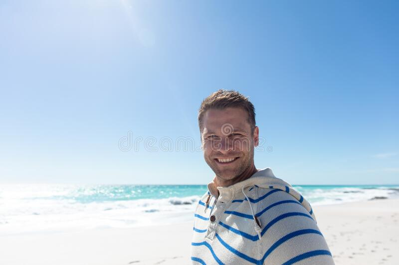 Man smiling at the beach. Front view of a Caucasian man standing on the beach with blue sky and sea in the background, smiling to camera royalty free stock photography