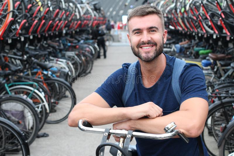 Man smiling in bicycle parking lot royalty free stock photo