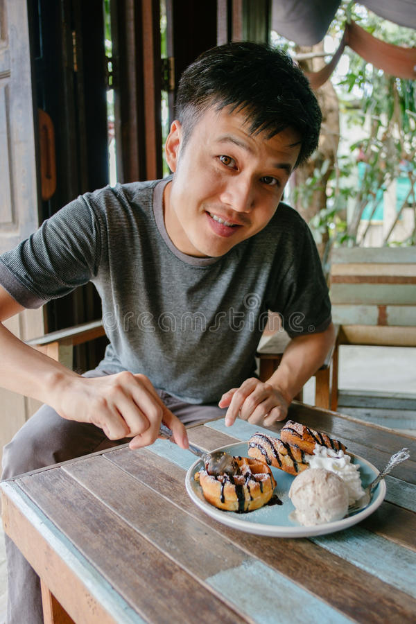 Man smiling eating waffle with ice-cream at vintage cafe stock image