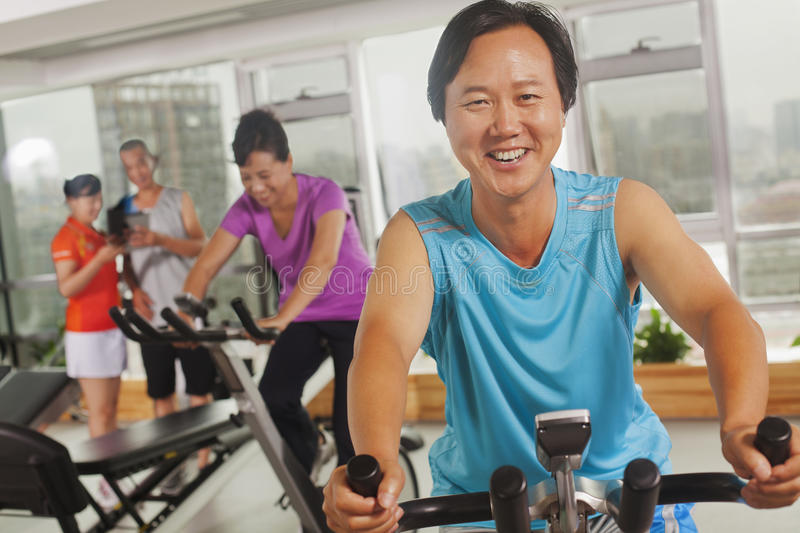 Man smiling and exercising on the exercise bike at the gym, looking at camera stock photo