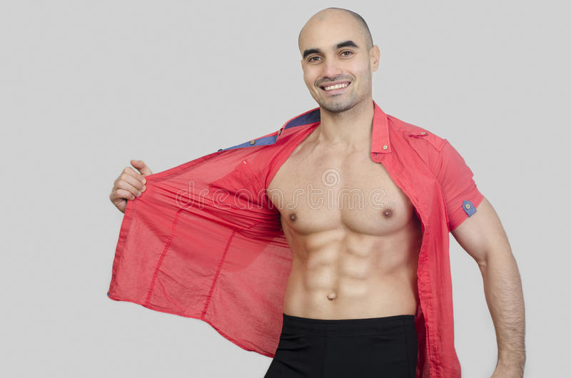 Man smiling showing abs. Happy man puling his shirt showing six pack abdominal stock photos