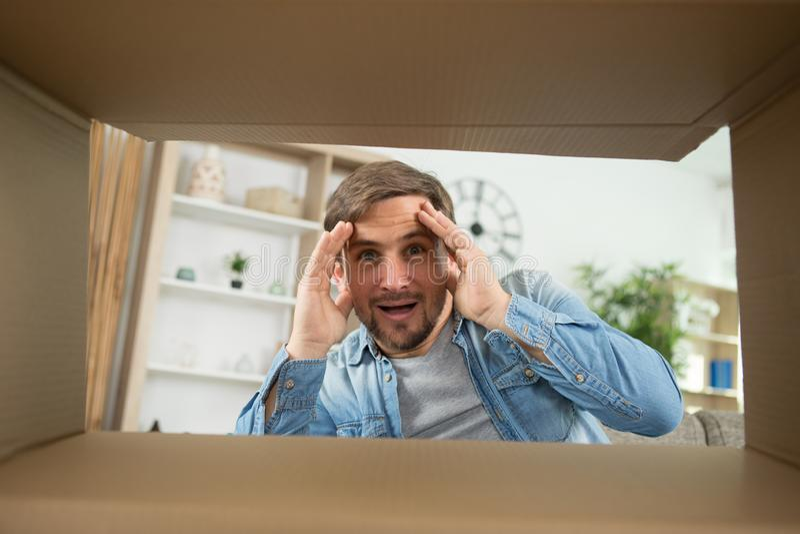 Man smiling unpacking opening carton box and looking inside stock image