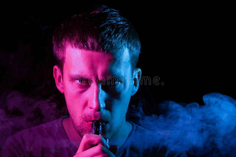 A man smokes an cigarette and exhales colored smoke in different directions on a black background royalty free stock photos
