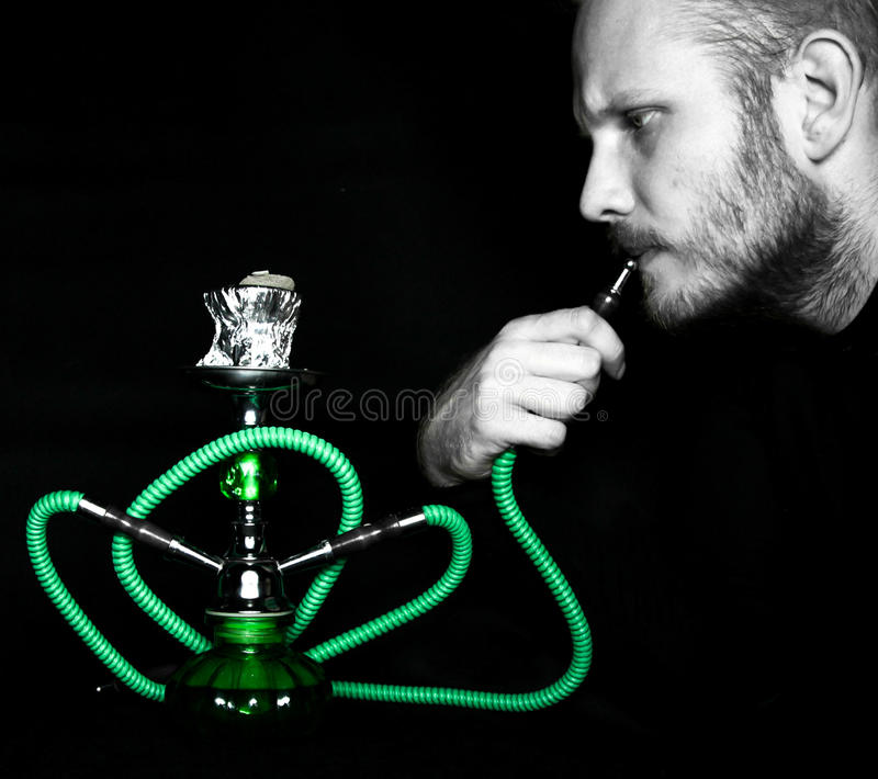 Man smokes a hookah. In studio royalty free stock images