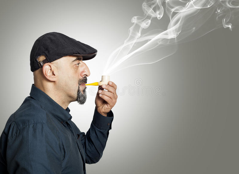 The man smokes a pipe. On gray background stock images