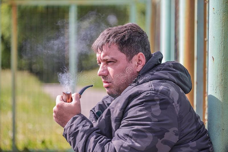 Man smokes a pipe. The man is smoking a pipe, close-up, in the cool windy weather, the smoke is flying in the air royalty free stock photography