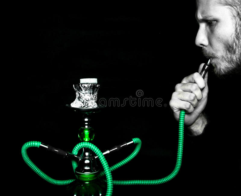 Man smokes a water pipe stock photos