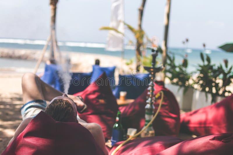 Man smoking hookah on a beach side restaurant next to the sea. Shisha smoking. Bali island. royalty free stock photo