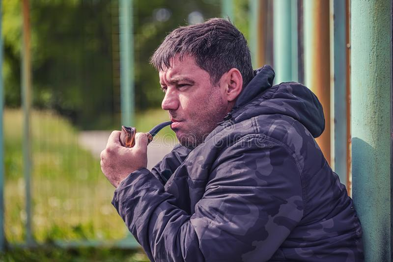 Man smokes a pipe. The man is smoking a pipe, close-up, in the cool windy weather, the smoke is flying in the air stock photo