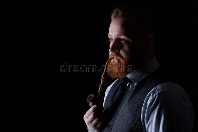 Man smoking a pipe. Portrait of a red bearded man smoking a pipe on black background royalty free stock photography