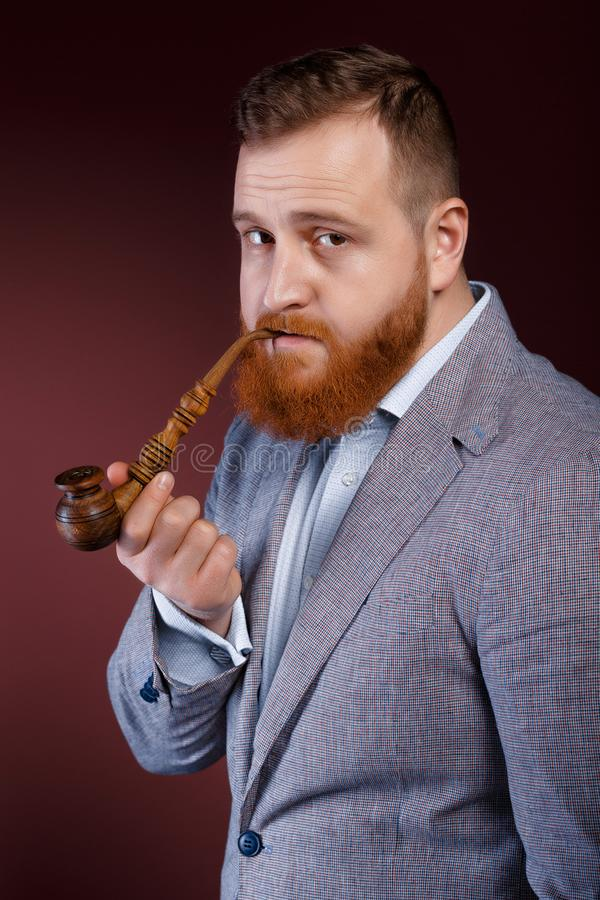 Man smoking a pipe. Portrait of a red bearded man smoking a pipe on a brown background royalty free stock image