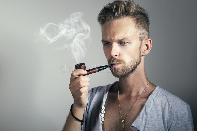 Man smoking pipe. Young handsome male smoking pipe stock photography