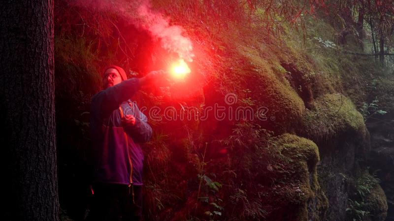 Man smoking red signal fire. Stock footage. Man got lost in woods during hike and lit flare. Young man on journey lost royalty free stock photography