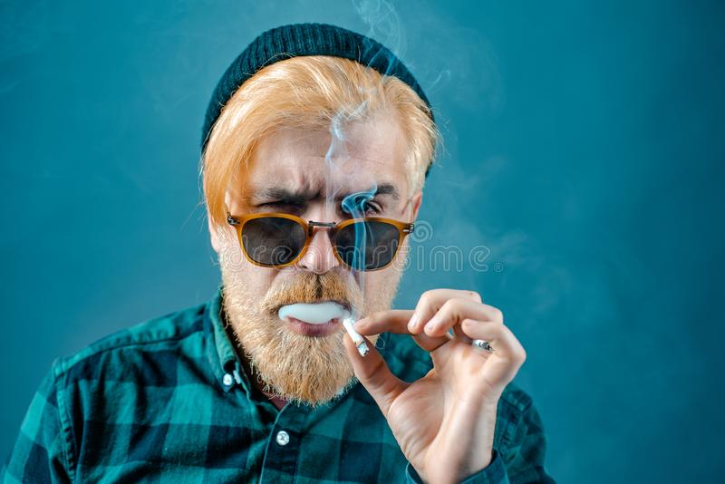 Man smoking. Sexy gorgeous stylish man. Close-up face of young bearded man on dark background - professional studio royalty free stock photography