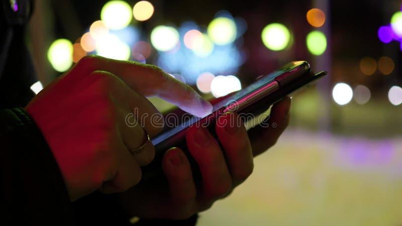 Man sms som smsar genom att använda app på smartphonen på natten i stad, vintertid closeup fotografering för bildbyråer