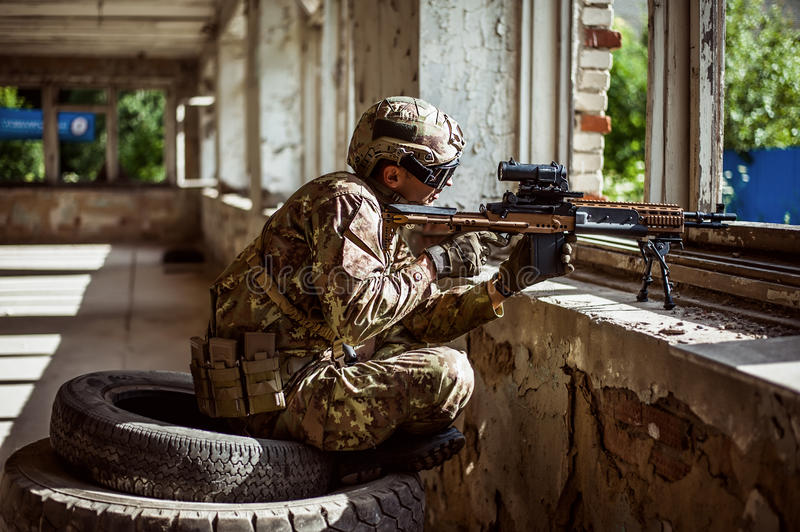 Man sniper with automatic rifle with a telescopic sight. Military man sniper with automatic rifle with a telescopic sight sitting by the window in building stock images