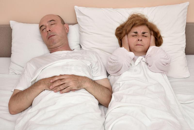 Man snoring while woman cannot sleep royalty free stock photography