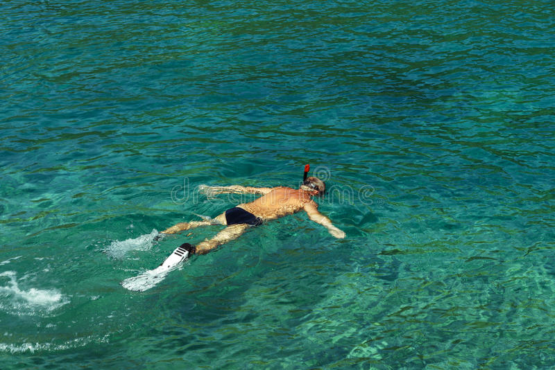Man snorkeling with flippers, mask and snorke in lazure, clear seawater of Adriatic Sea. Flecks of sunlight in the seawater. Top v royalty free stock photography