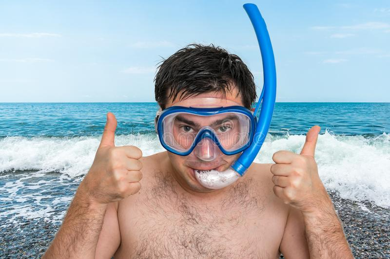 Man with snorkeling mask for diving stands near the sea stock photo