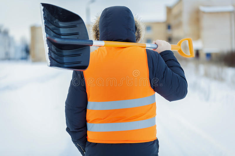Man with snow shovel near building in winter stock photography