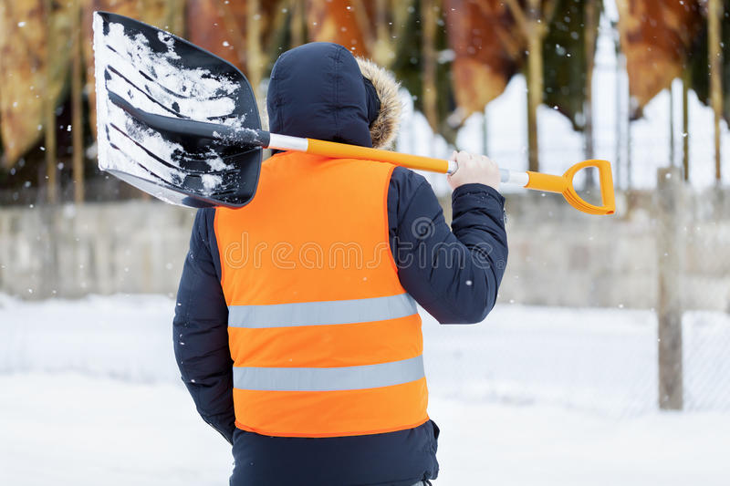 Man with snow shovel near tanks in winter stock images