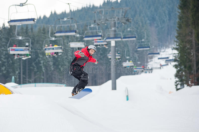 Man on the snowboard jumping over the slope. In winter day with snow-covered firs and ski lifts in background at a winter resort, Bukovel, Ukraine royalty free stock photos