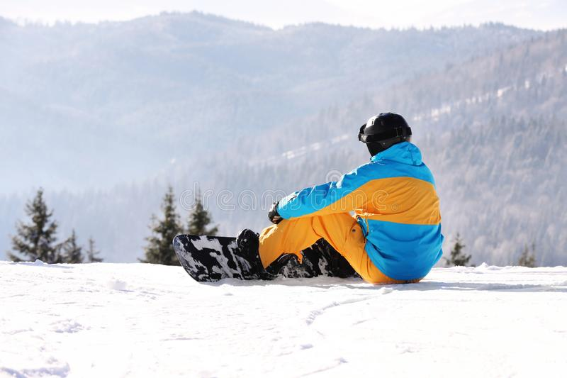 Man with snowboard resting in mountains. Winter stock photos