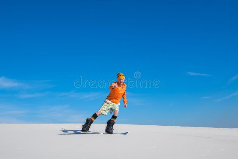 Man on snowboard, riding on sand slope. stock photos