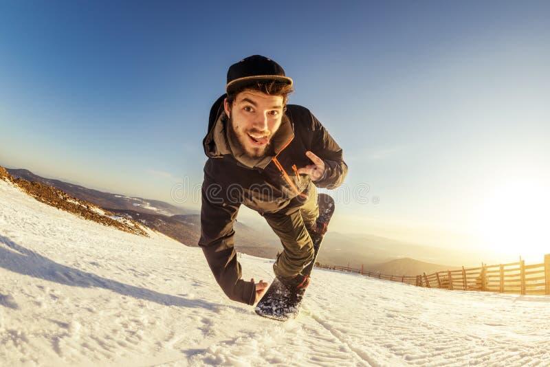 Man snowboarder playful jump trick stock images