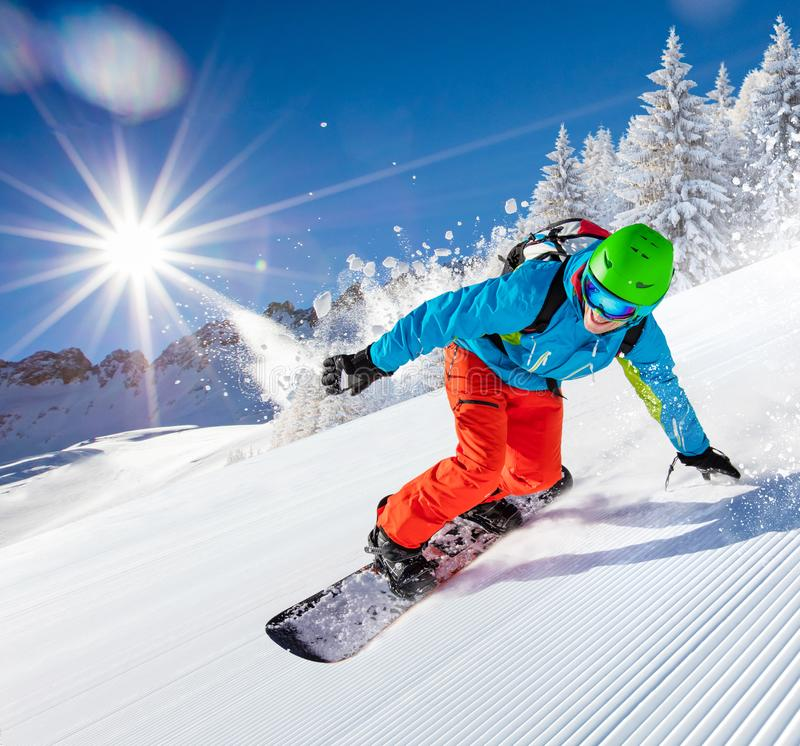 Man snowboarder riding on slope. royalty free stock photography