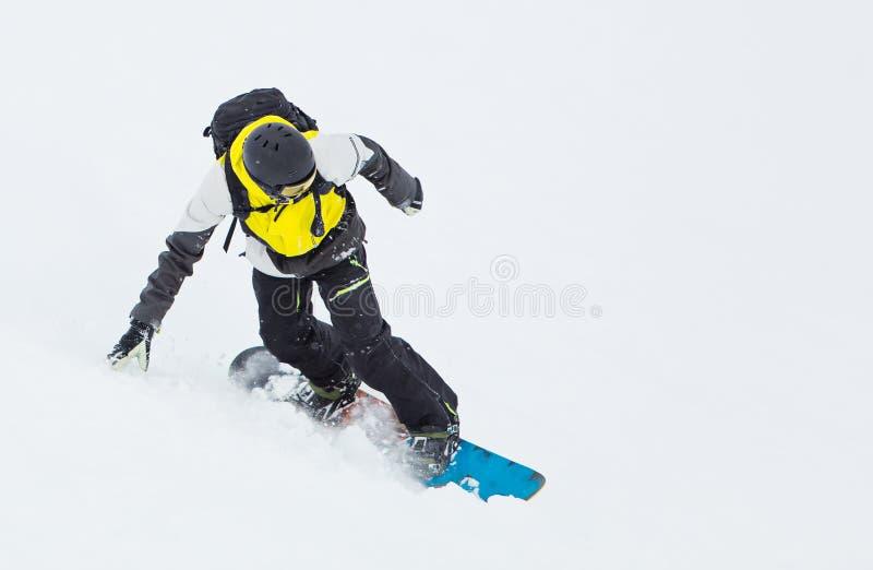 Man snowboarder riding on slope. stock image