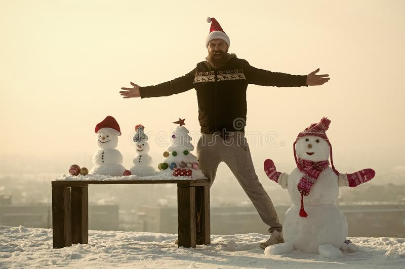 Man and snowman with open hands on white sky royalty free stock photo